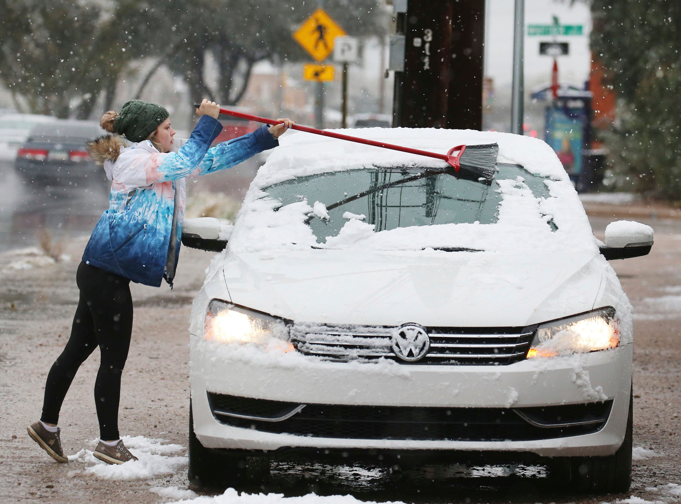 Ambria Dell'Oro uses a broom to wipe the collected snow from her car Friday, Feb. 22, 2019, in Tucson, Ariz.  Snow fell and accumulated in central and downtown Tucson on Friday, surprising many in a city where snow is extremely rare.