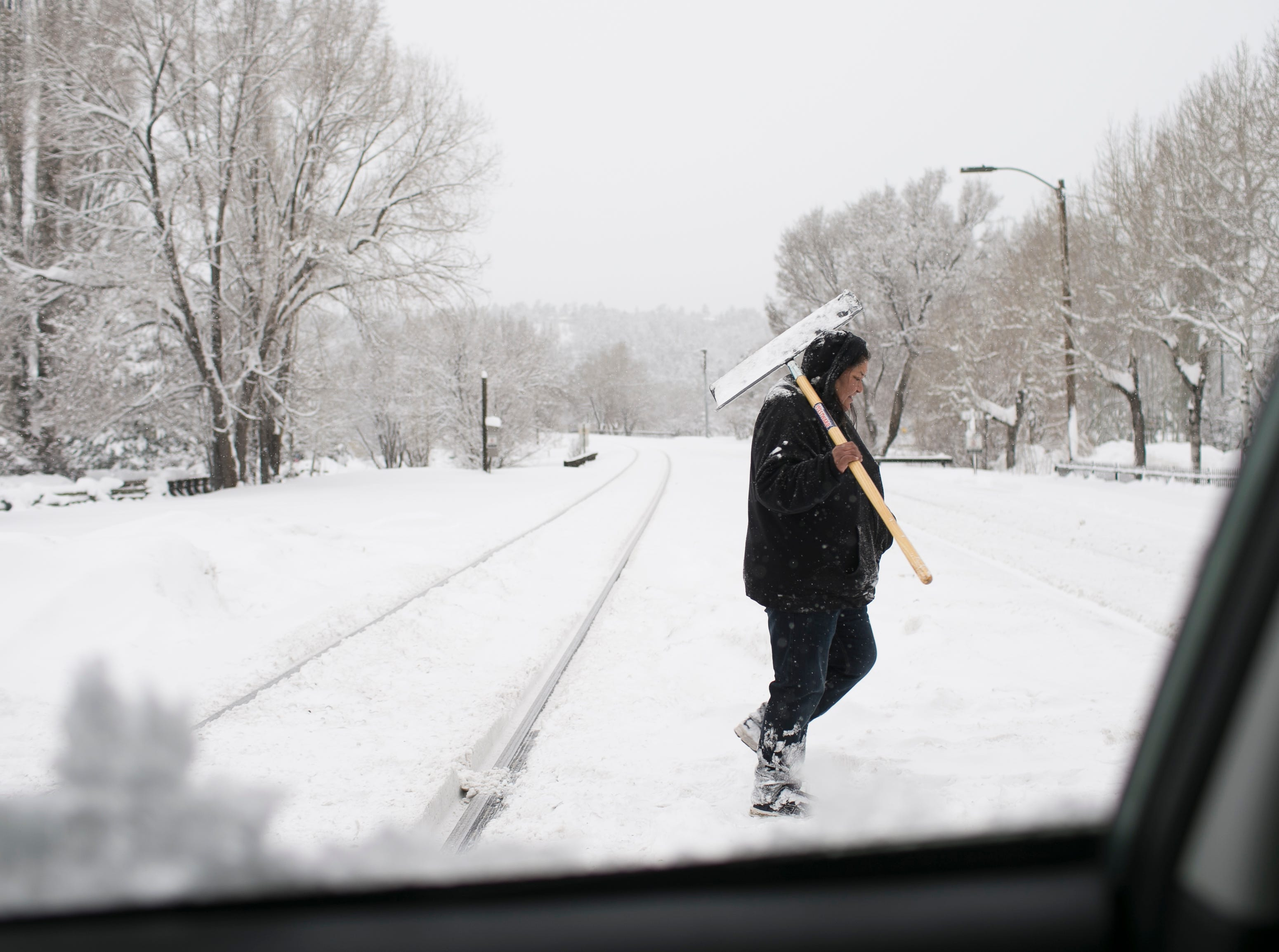 Pablena Honyumptawa carries a shovel to clean up snow the morning after a storm in Flagstaff on Feb. 22, 2019.