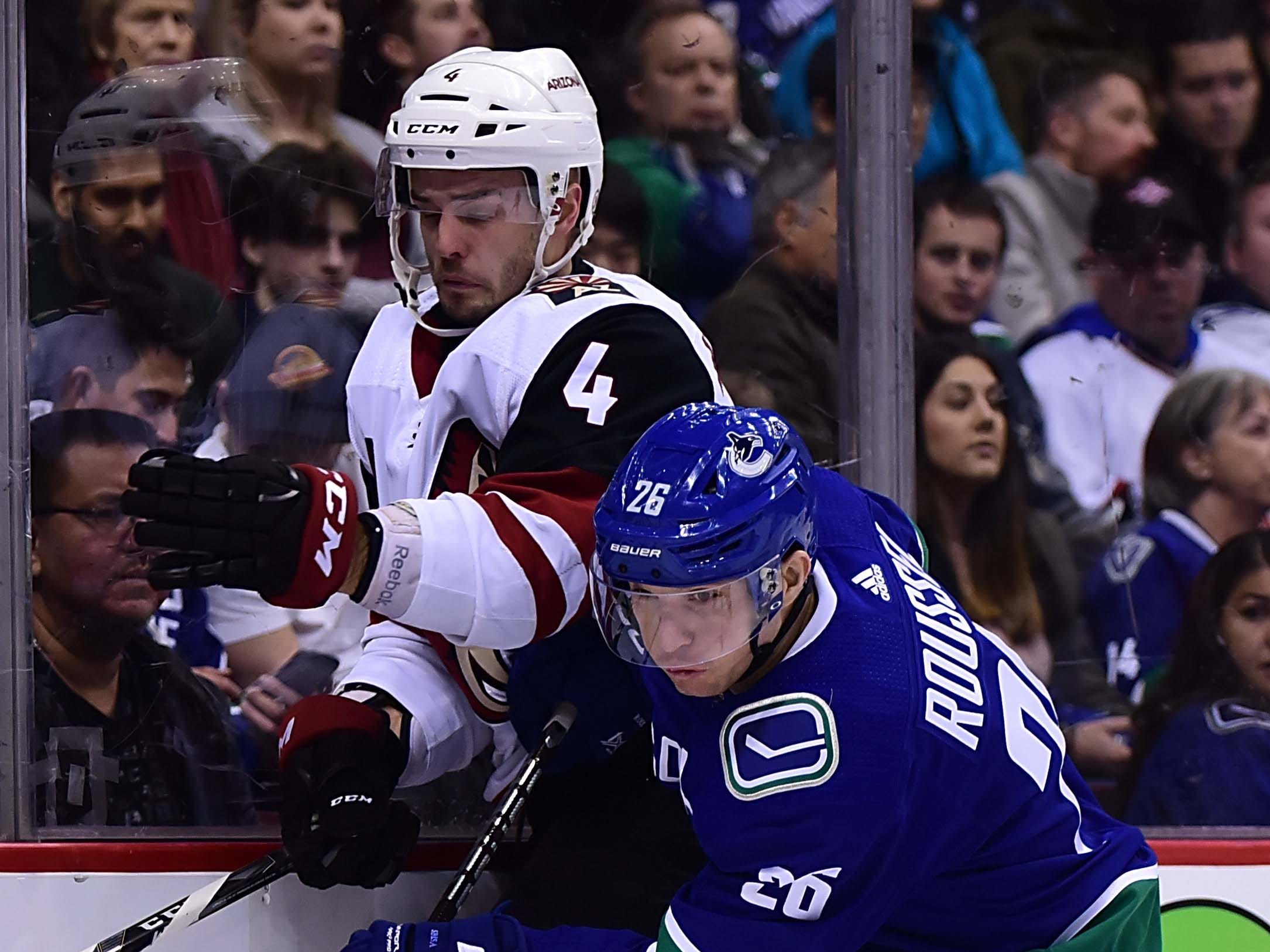 Feb 21, 2019; Vancouver, British Columbia, CAN; Vancouver Canucks forward Antoine Roussel (26) checks Arizona Coyotes defenseman Niklas Hjalmarsson (4) during the first period at Rogers Arena. Mandatory Credit: Anne-Marie Sorvin-USA TODAY Sports