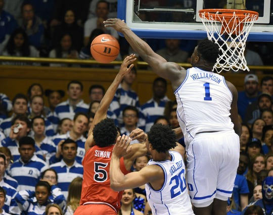 Zion Williamson blocks a shot from St. John's guard Justin Simon during a game at Cameron Indoor Stadium.