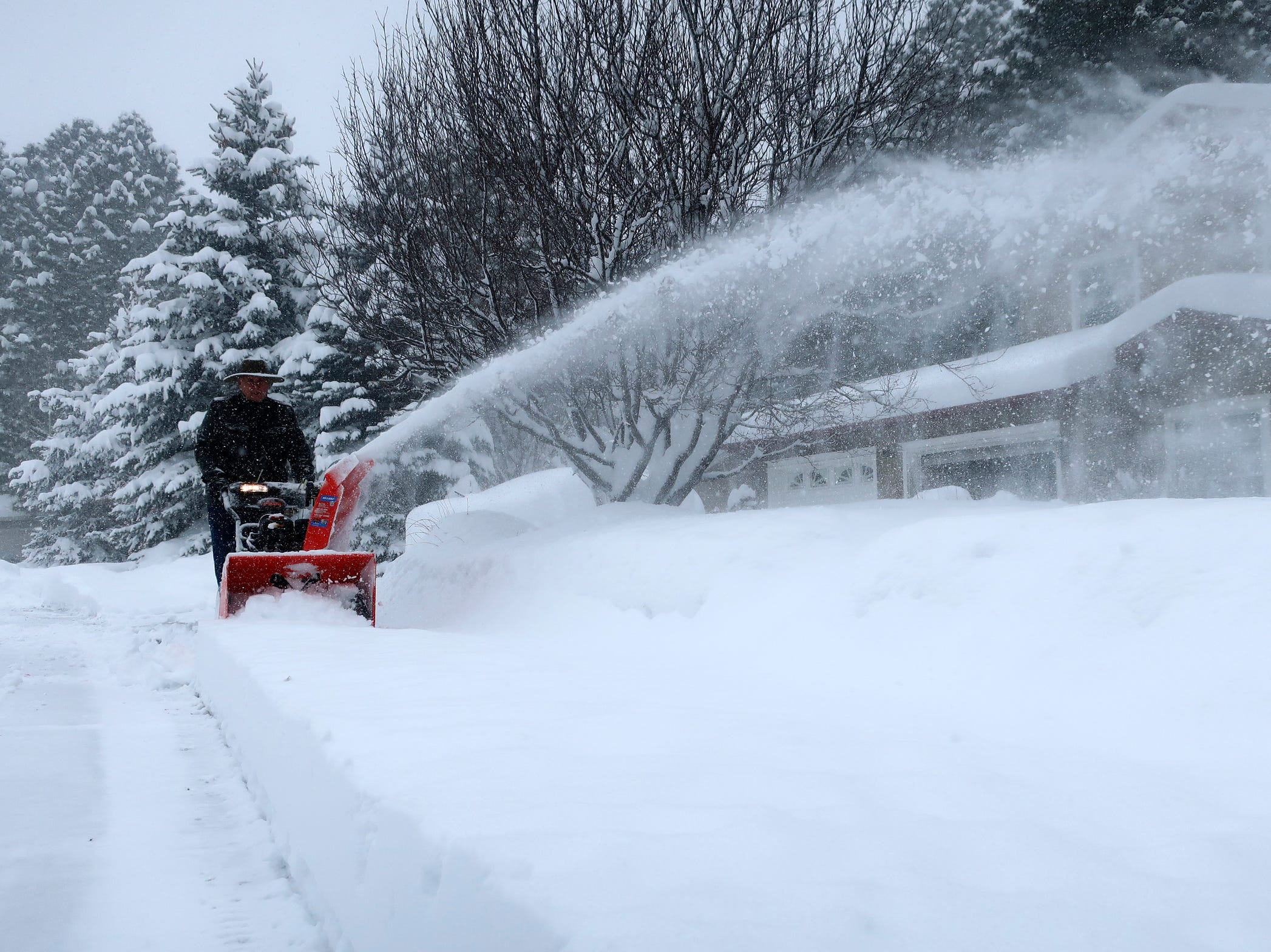 Richard Henn runs a snow blower down the sidewalk outside his home in Flagstaff, Arizona, on Thursday, Feb. 21, 2019. Schools across northern Arizona canceled classes and some government offices decided to close amid a winter storm that's expected to dump heavy snow in the region.