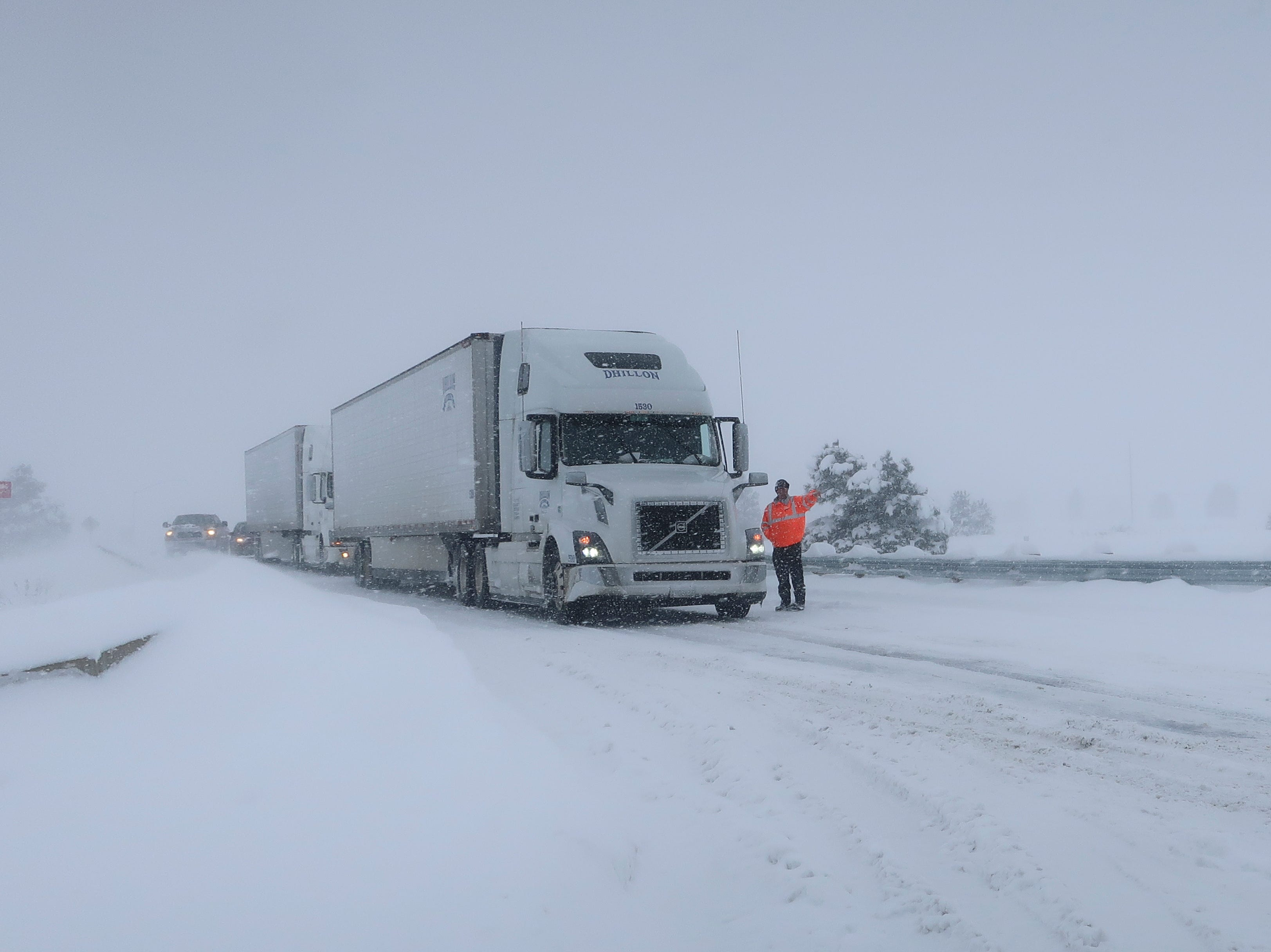 Frank Van Buren, the manager of a travel center, gives direction to semi-truck drivers who are pulling off Interstate 40 in Bellemont, Arizona, on Thursday, Feb. 21, 2019. Feb. 21, 2019. Schools across northern Arizona canceled classes and some government offices decided to close amid a winter storm that's expected to dump heavy snow in the region.