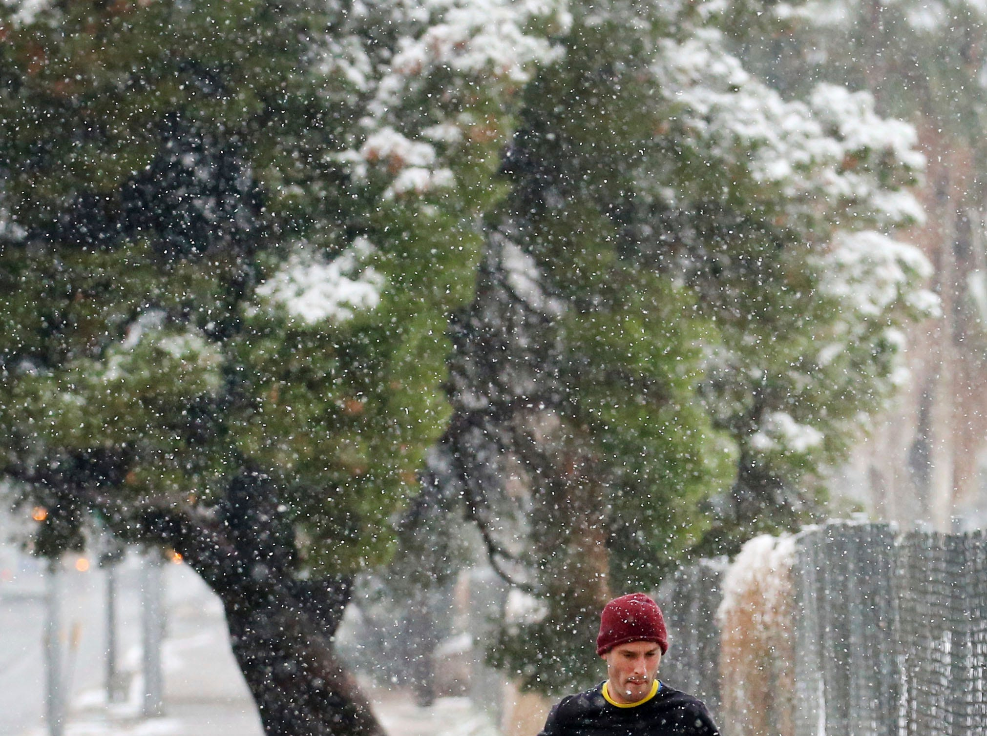 A jogger runs around the Randolph Golf complex, Friday, Feb. 22, 2019, in Tucson, Ariz.  Snow fell and accumulated in central and downtown Tucson on Friday, surprising many in a city where snow is extremely rare.