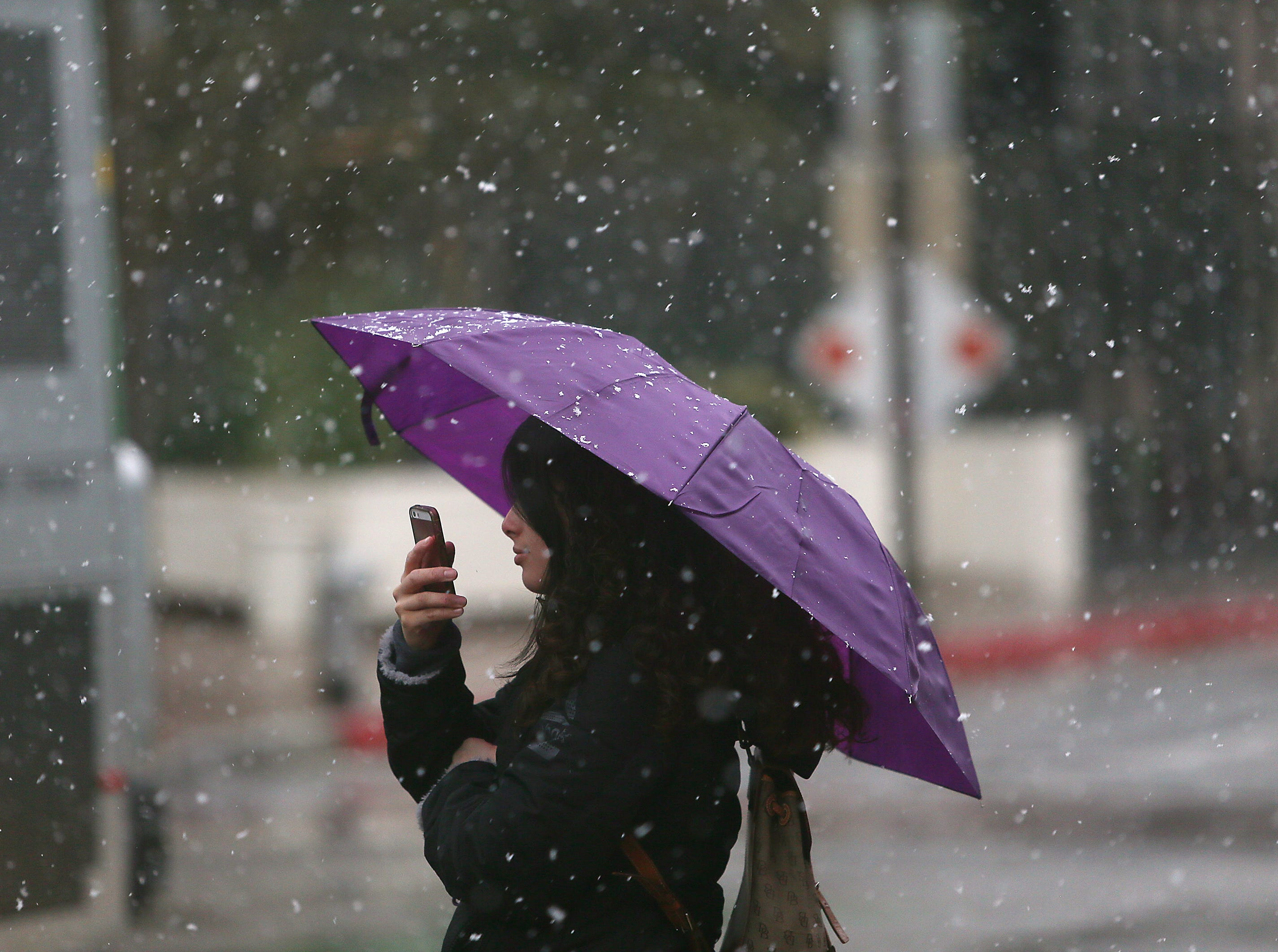 A woman takes a photo with her cellphone as snow falls on Feb. 22, 2019, in Tucson.