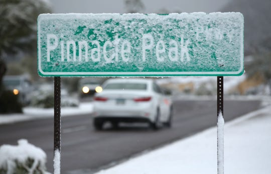 A Pinnacle Peak Road sign is covered in snow after a powerful winter storm brought six inches of snow to the area on Feb. 22, 2019 in Scottsdale, Ariz.