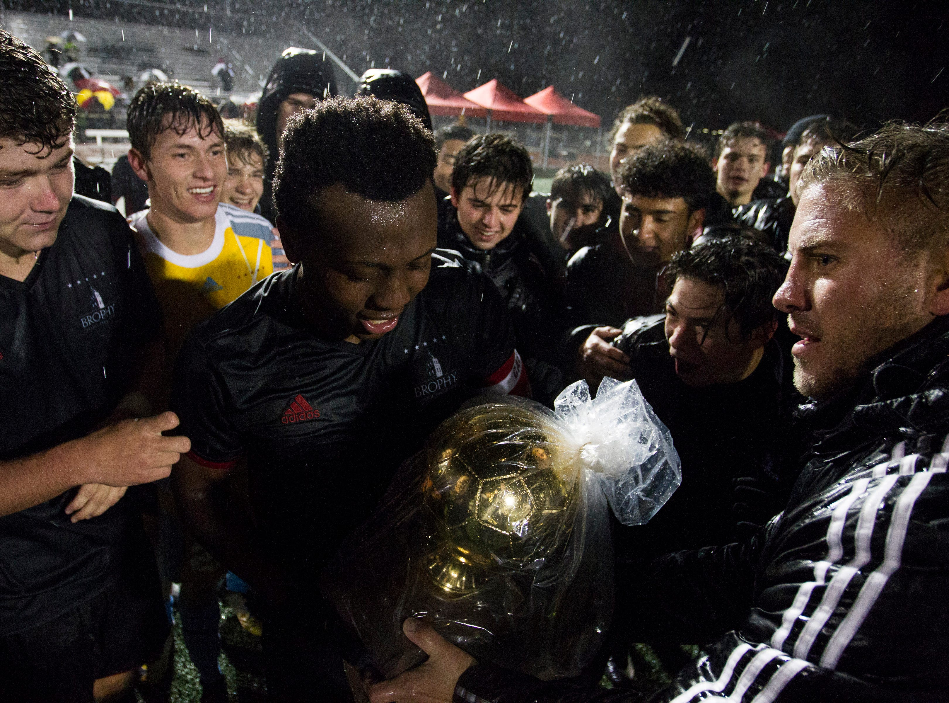 Brophy head coach Paul Allen hands over the gold ball to his captain Deric Hall after they won the 6A State Championship game over Hamilton 3-0 in Gilbert, Thursday, Feb 21, 2019.