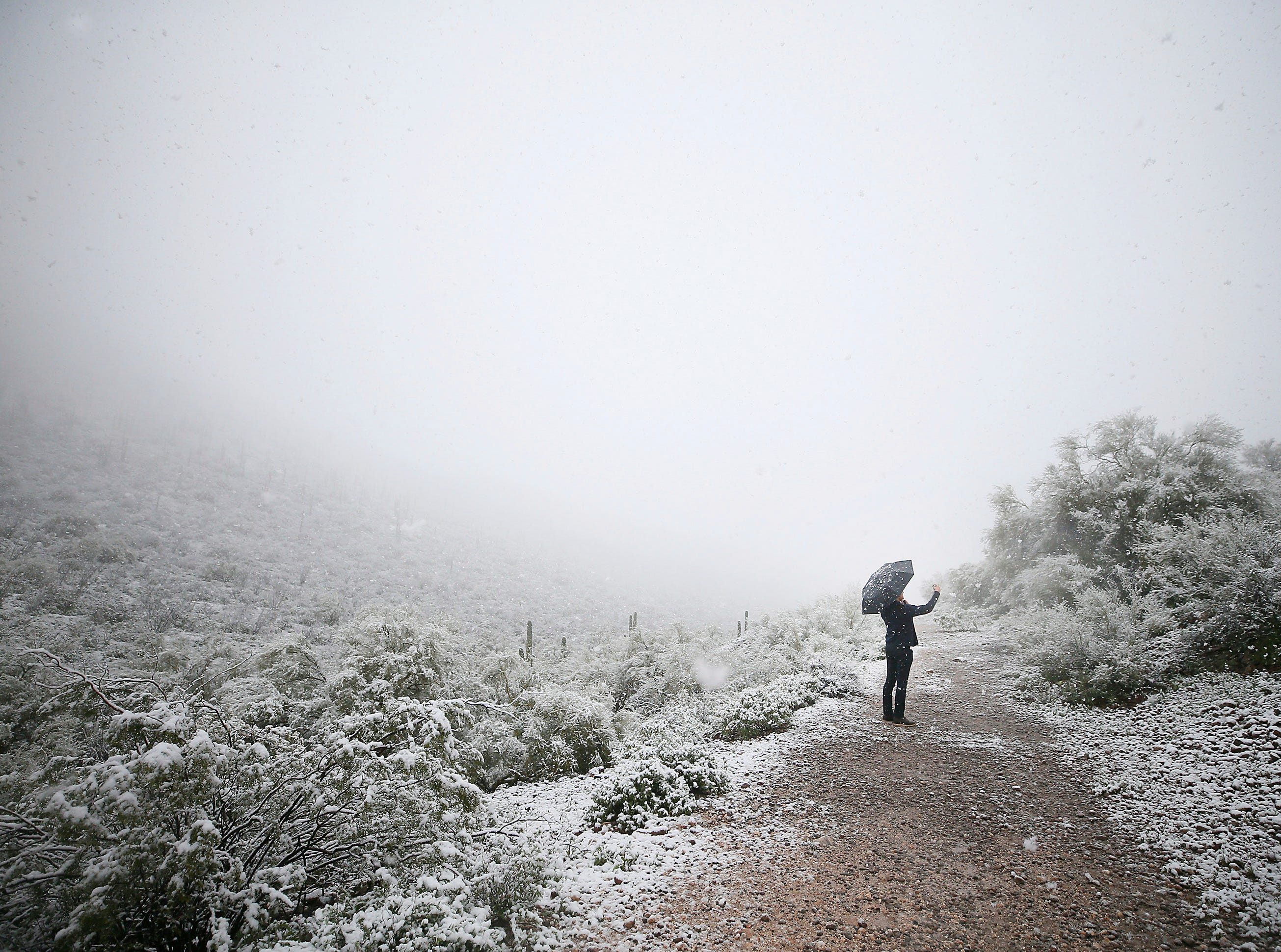 A man takes a photo of the desert landscape near Sentinel Peak covered in snow on Friday, Feb. 22, 2019, in Tucson, Ariz.  Snow fell and accumulated in central and downtown Tucson on Friday, surprising many in a city where snow is extremely rare.