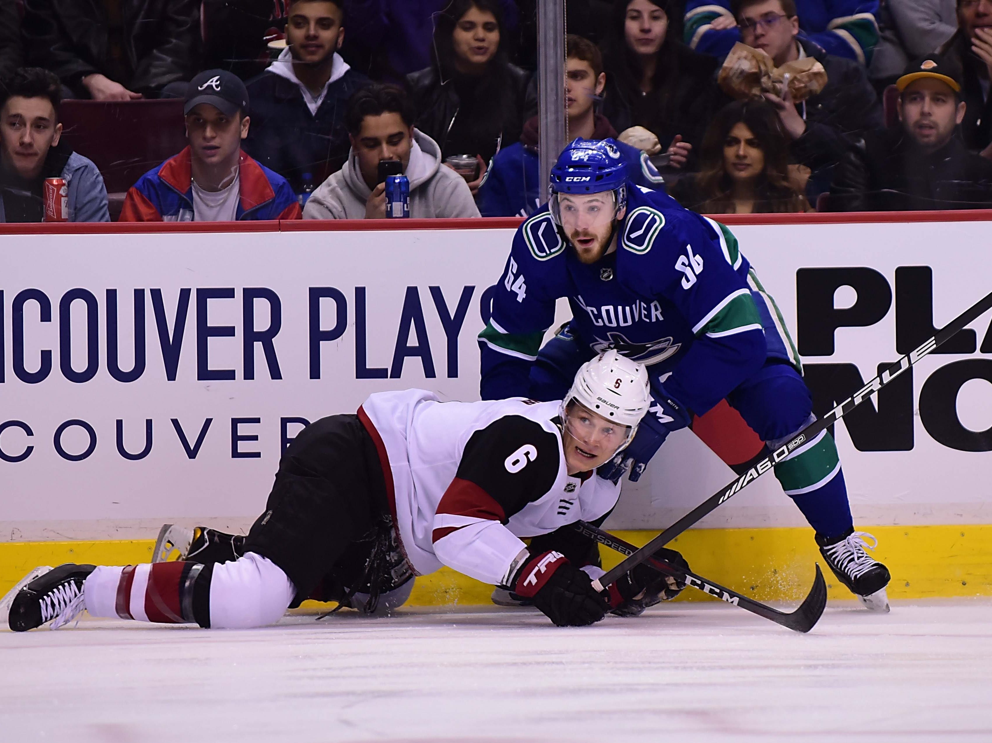 Feb 21, 2019; Vancouver, British Columbia, CAN; Vancouver Canucks forward Tyler Motte (64) checks Arizona Coyotes defenseman Jakob Chychrun (6) during the first period at Rogers Arena. Mandatory Credit: Anne-Marie Sorvin-USA TODAY Sports