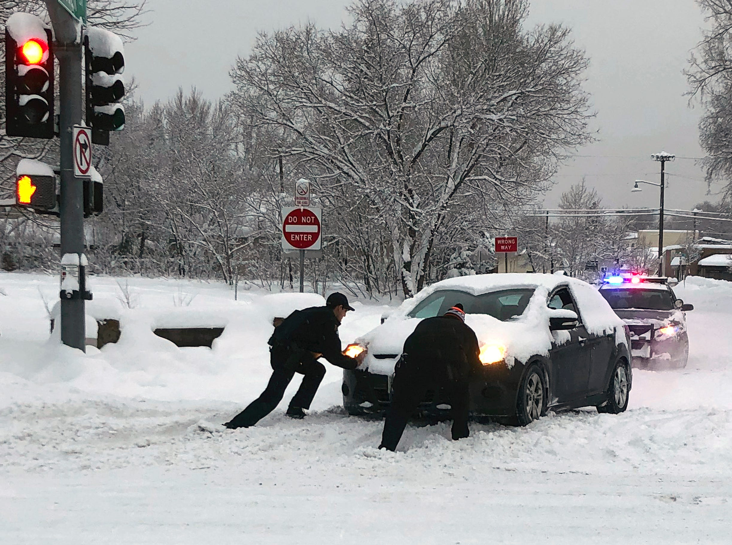 "This photo provided by the Flagstaff, Ariz., Police Department shows a police officer, left, helping a motorist push a car stuck in snow in Flagstaff Friday morning, Feb. 22, 2019. Schools, public libraries and businesses remained closed for a second day Friday amid a major, record-breaking storm in north-central Arizona. Snow fell Thursday at 3 to 4 inches (7.6 to 10.2 centimeters) an hour in what the National Weather Service characterized as ""not your average"" storm. The heaviest precipitation was pushing further into eastern Arizona before the storm moves out over the weekend, leaving temperatures at or below freezing."