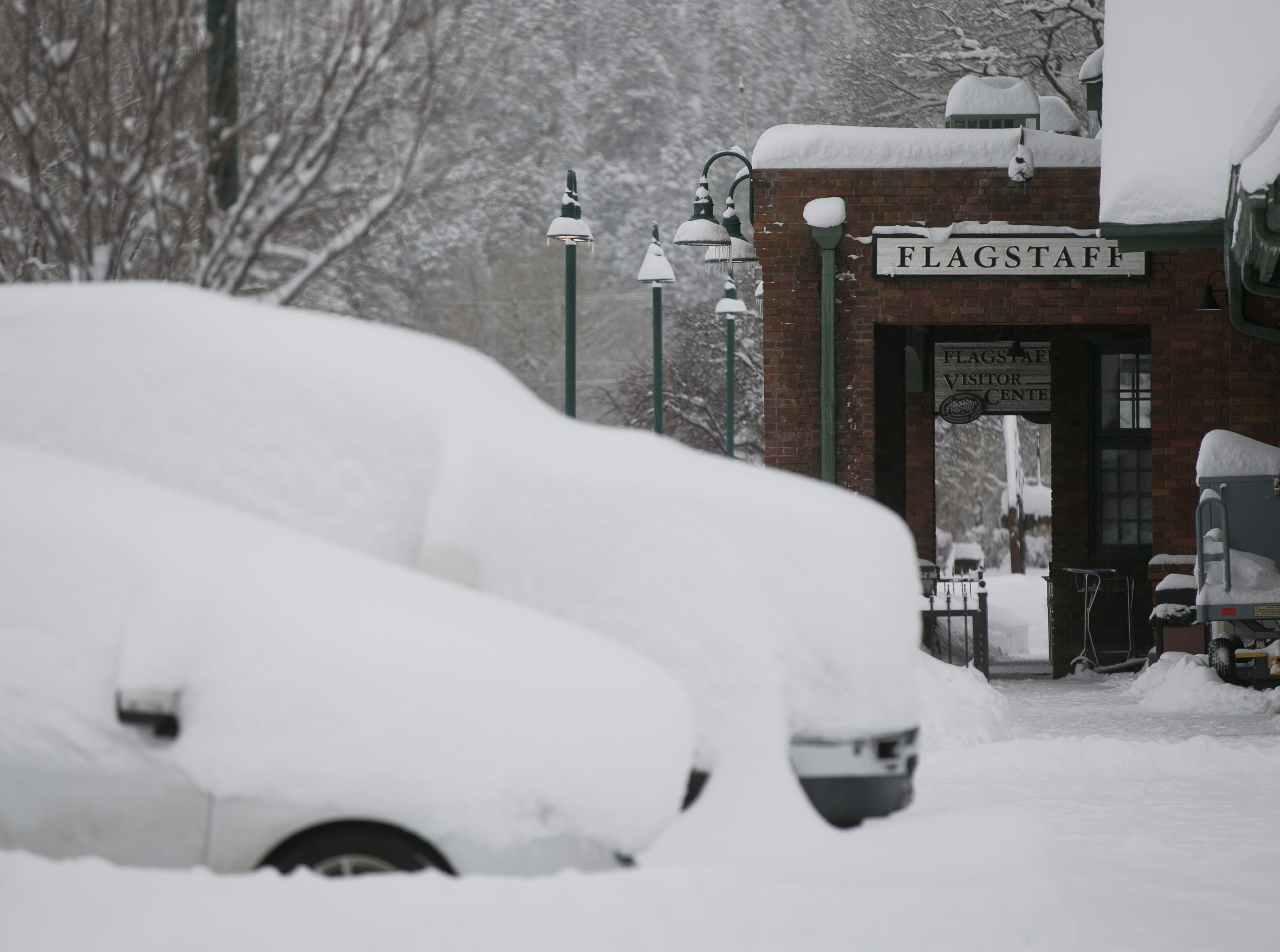Snow blankets cars in front of the Flagstaff visitors center the morning after a snow storm in Flagstaff on Feb. 22, 2019. The day before, a snow storm set the record for the most amount of snowfall in a day in Flagstaff