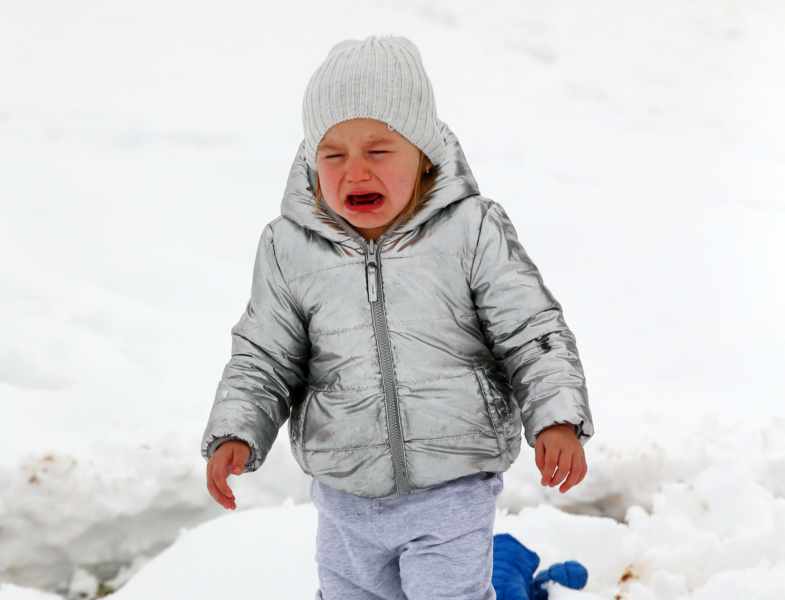 Georgia Lentine, age 2 of Phoenix cries during her first experience with snow after a winter storm brought six inches of snow on Feb. 22, 2019 in Scottsdale, Ariz.