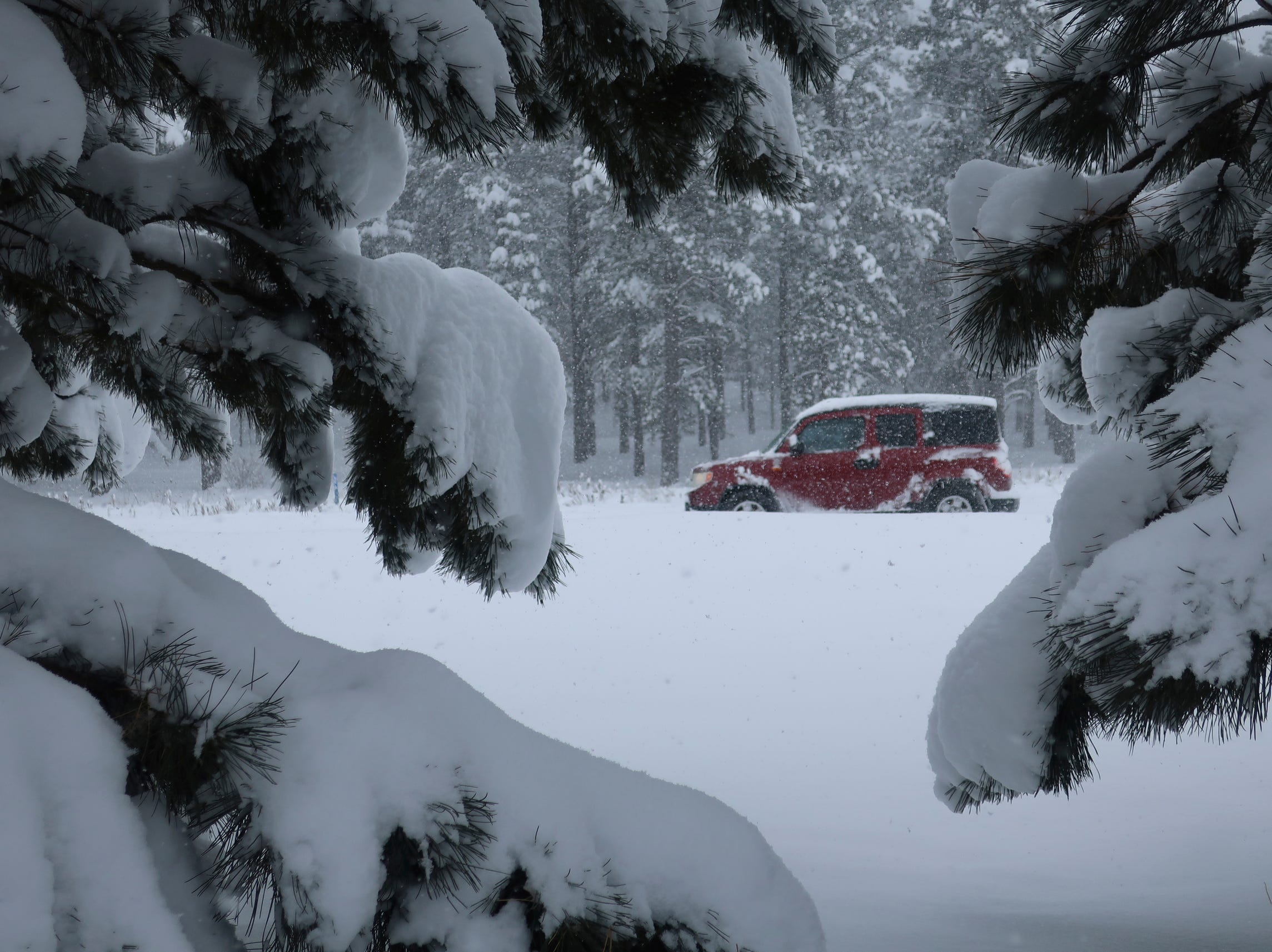 A car drives down Route 66 in Flagstaff, Arizona, on Thursday, Feb. 21, 2019. Schools across northern Arizona canceled classes and some government offices decided to close amid a winter storm that's expected to dump heavy snow in the region.