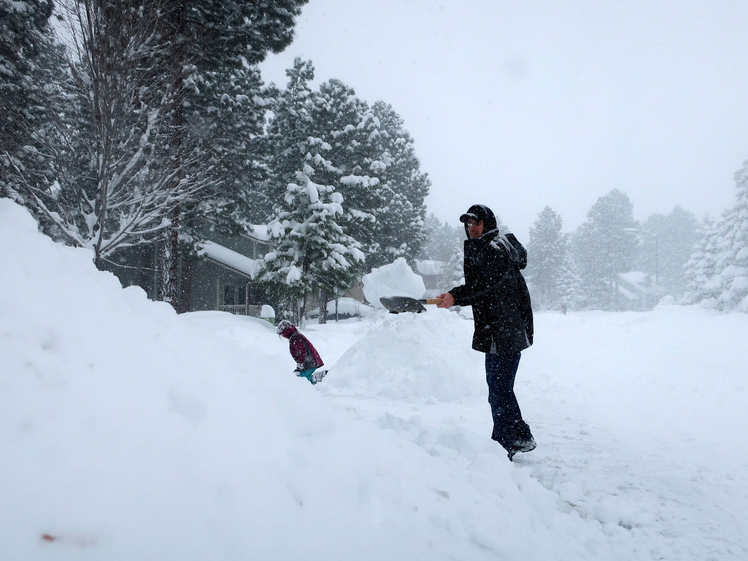 Morgan Baggs shovels the driveway at his home in Flagstaff, Arizona, on Thursday, Feb. 21, 2019. Schools across northern Arizona canceled classes and some government offices decided to close amid a winter storm that's expected to dump heavy snow in the region.