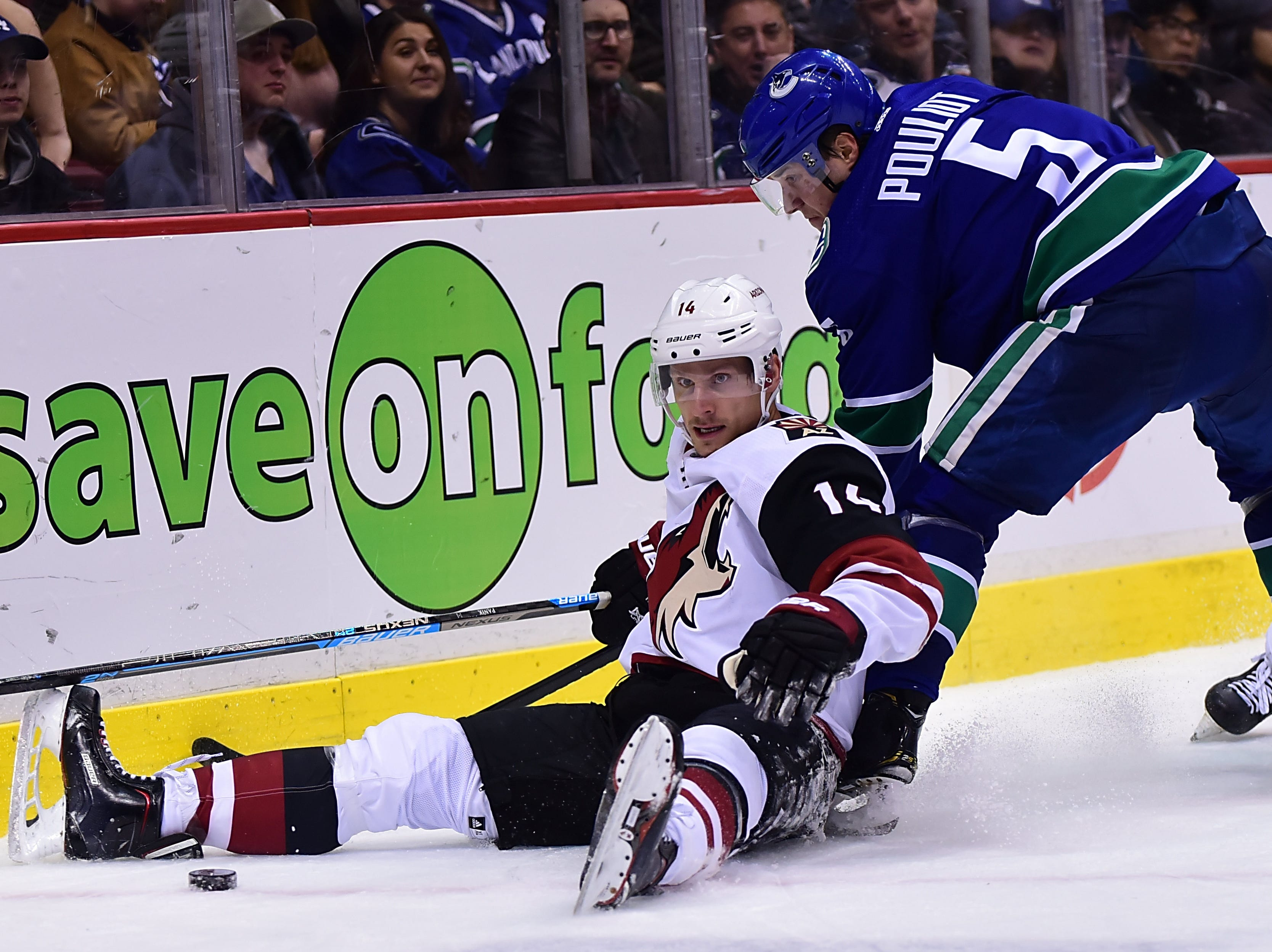 Feb 21, 2019; Vancouver, British Columbia, CAN; Arizona Coyotes forward Richard Panik (14) battles for the puck against Vancouver Canucks defenseman Derrick Pouliot (5) during the second period at Rogers Arena. Mandatory Credit: Anne-Marie Sorvin-USA TODAY Sports