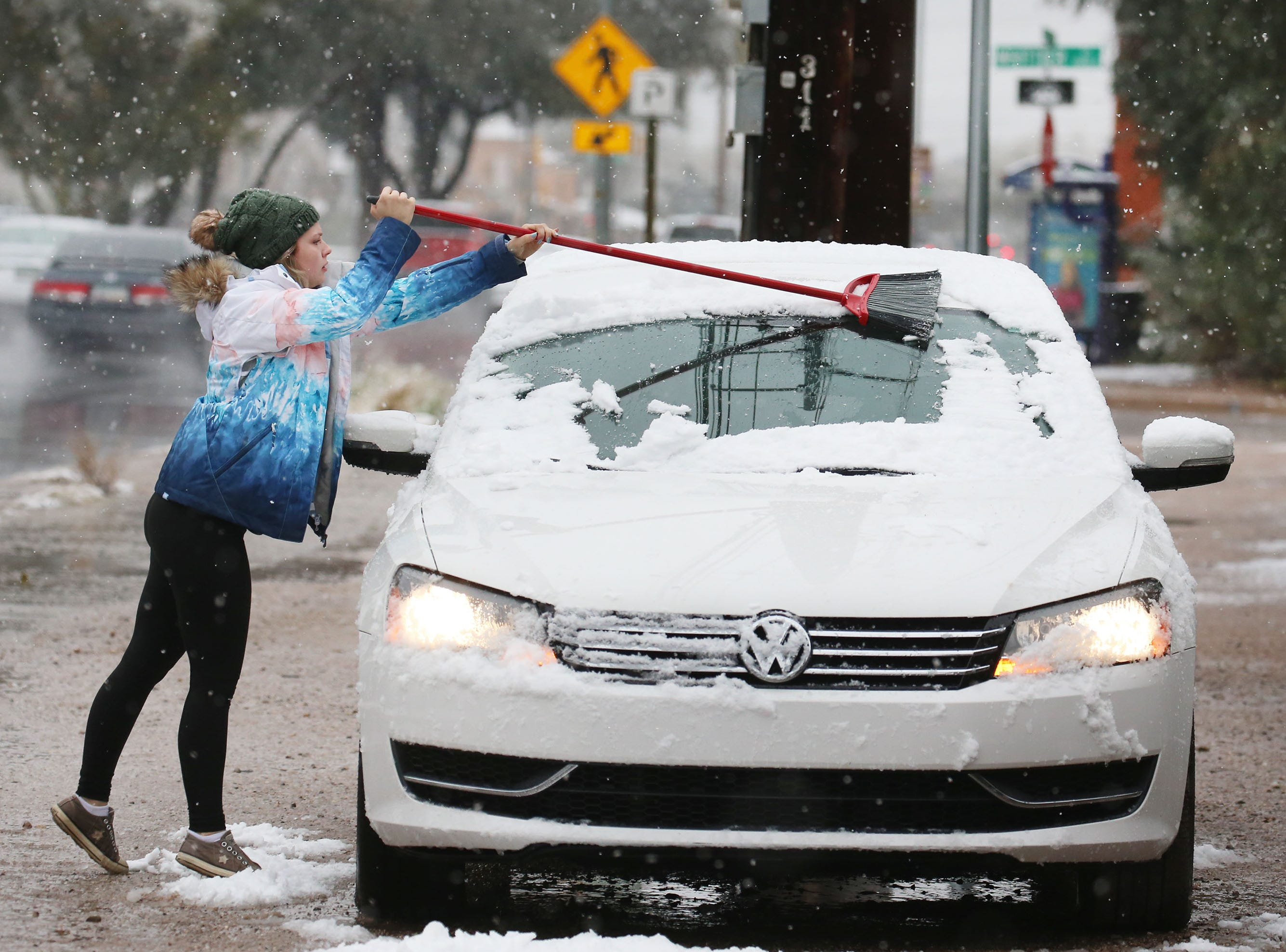Ambria Dell'Oro, a New Jersey native, uses a broom to wipe the collected snow from her Volkswagen in midtown as the metro Tucson area receives snowfall following a late February storm system, Feb. 22, 2019, in Tucson, Ariz.
