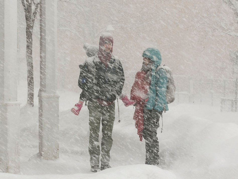 Sienna Chapman (right) carries her 6-month-old son Aldo Bransky on her chest (center-right) as she walks with Nat Bransky (left) carrying their 3-year-old daughter June Bransky on his back through the snow in downtown Flagstaff on Thursday, Feb. 21, 2019. A storm was expected to bring 20-30 inches of snow around northern Arizona through Friday.