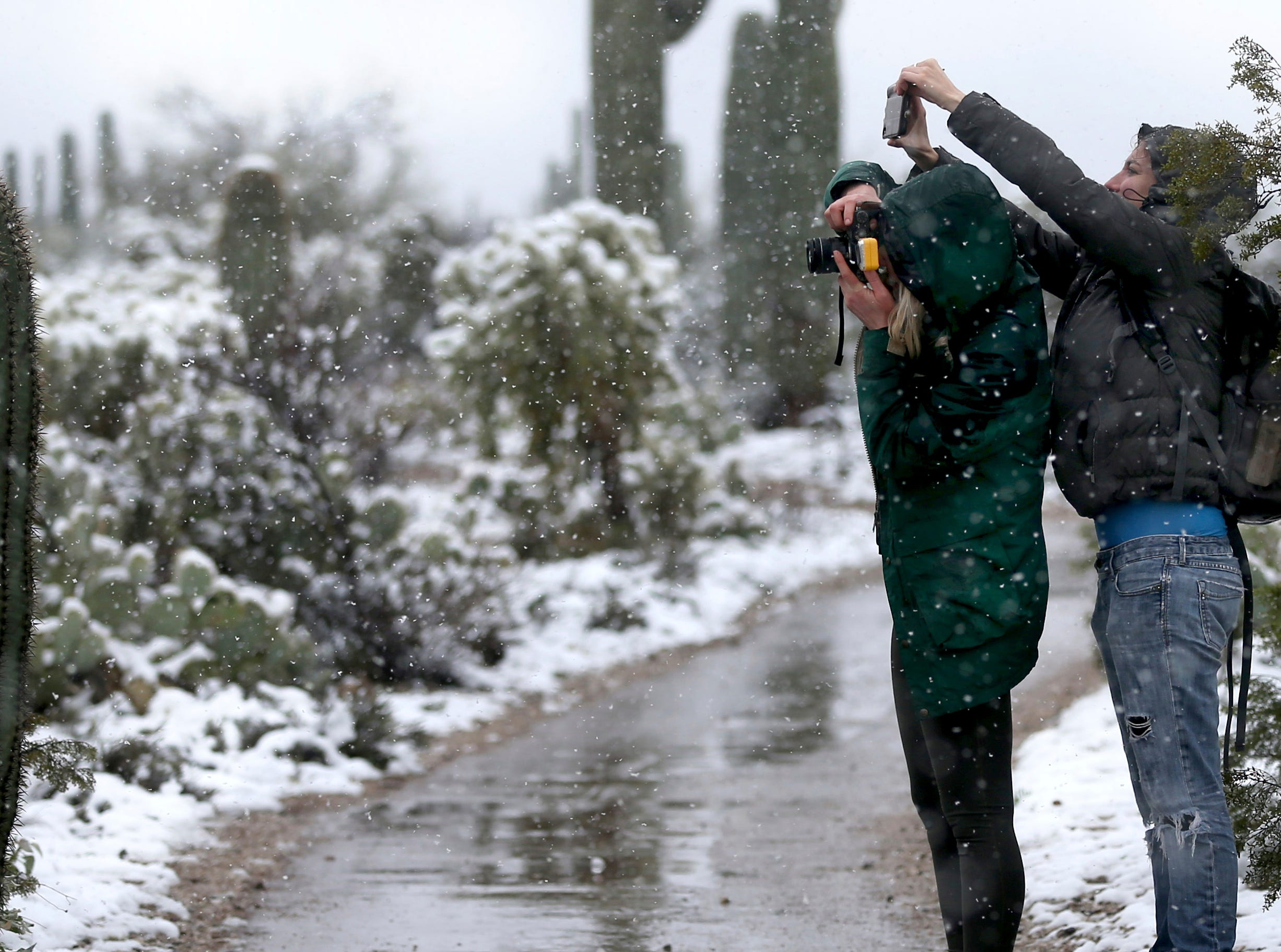 Julia DeConcini, left, and Brittany Smith take photos of the snowman they found and moved to the top of a nearby cactus while taking in the sight of snow over Saguaro National Park East, Friday, Feb. 22, 2019, in Tucson, Ariz. A winter storm dumped record-breaking amounts of snow in Arizona and forced the closure Friday of roads, schools and government offices across the Southwest.