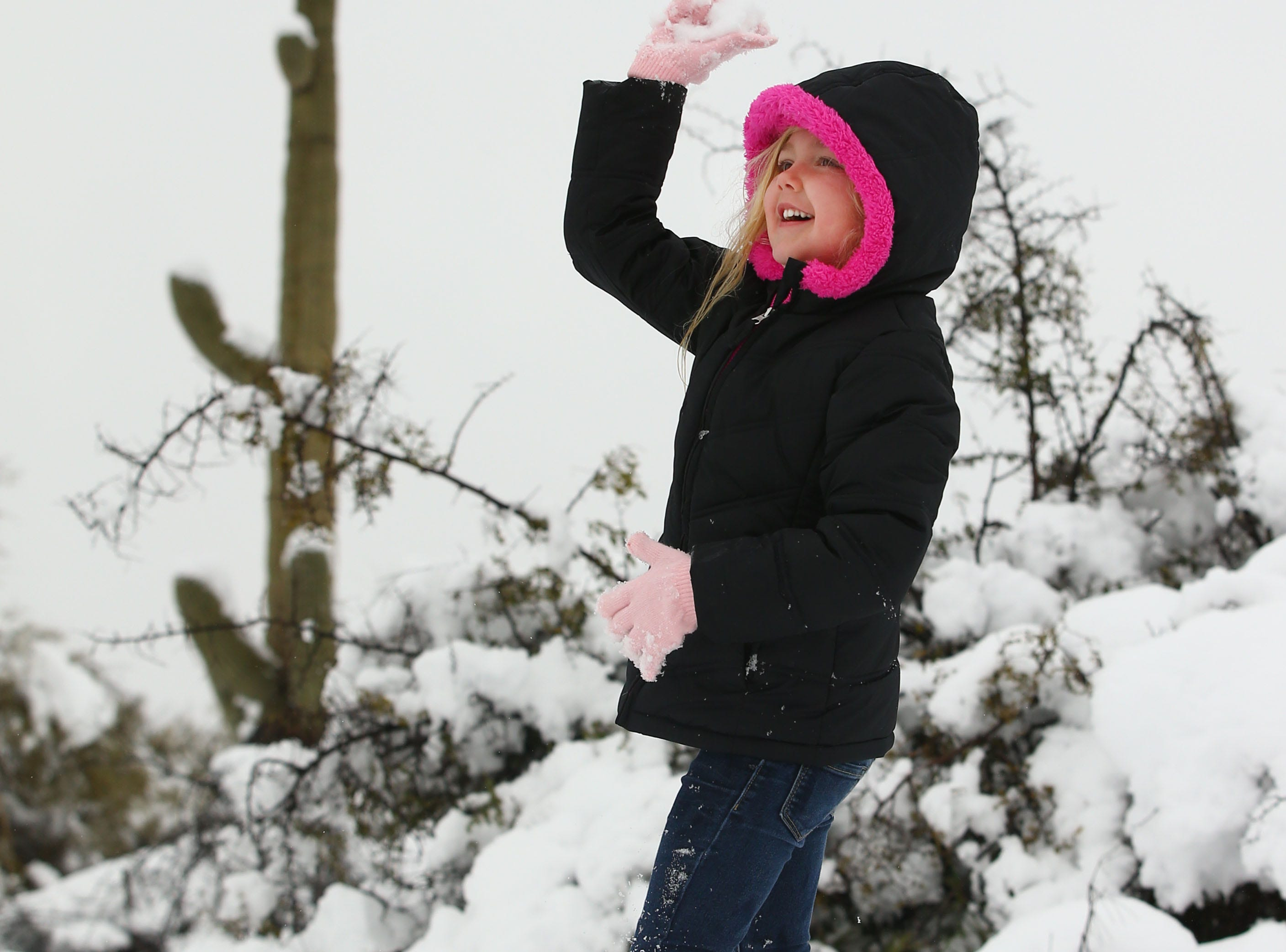 Ashlee Martin, age 5 has a snowball fight with a saguro cactus in the background after a winter storm brought six inches of snow on Feb. 22, 2019 in Scottsdale, Ariz.