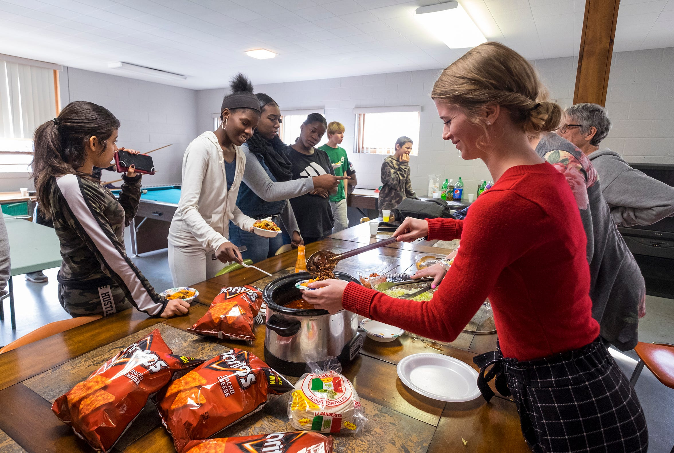 Difference Makers volunteer Lauren Jones, right, serves lunch to a group of teens Thursday, Feb. 21, 2019 in a room on the Center's second floor. Difference Makers began hosting programs at the Center in March 2018.
