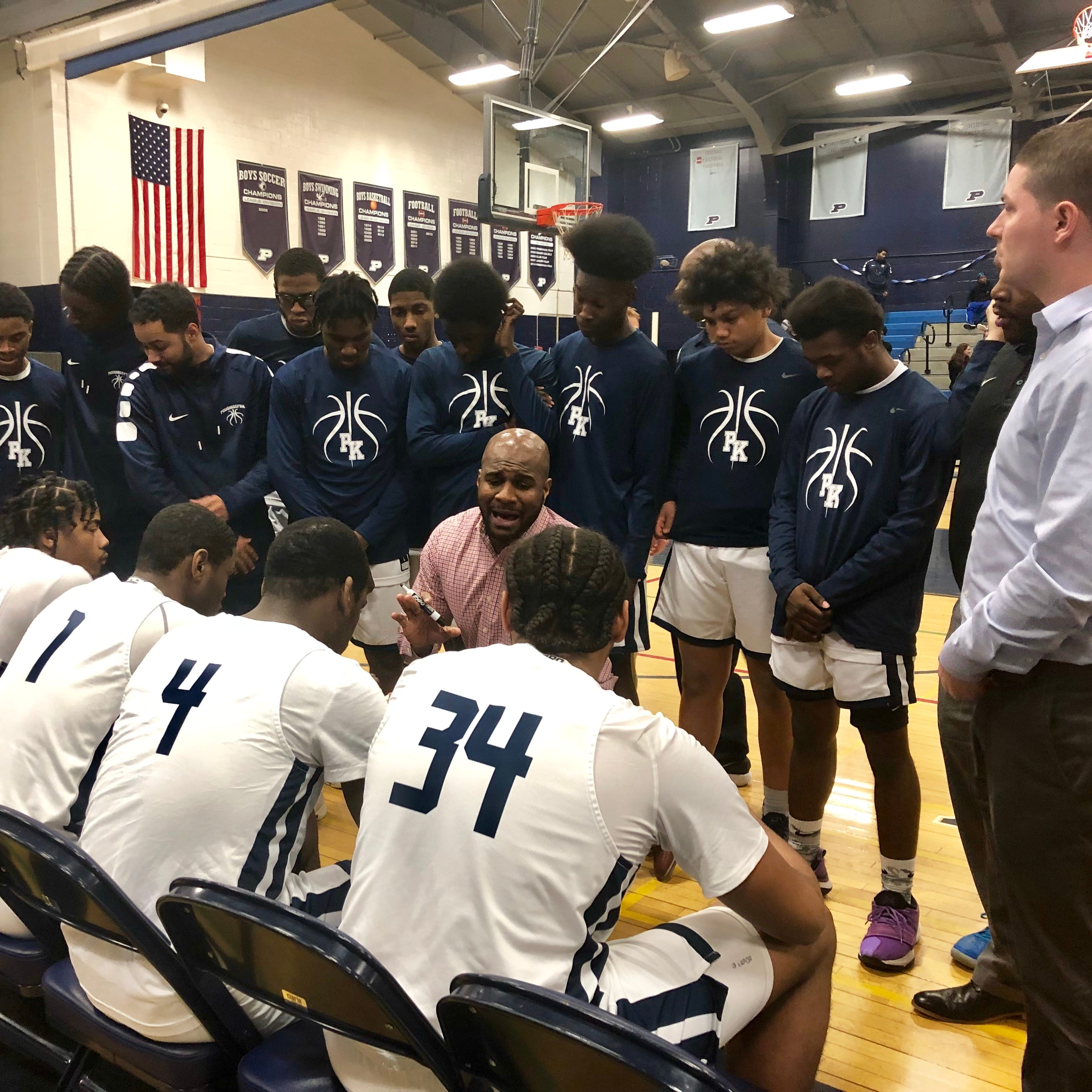 Poughkeepsie coach Cody Moffett discusses strategy with his boys basketball team during their Section 1 Class A playoff game against Pearl River.
