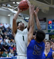 Josh Rolling goes up to shoot against Reed's Neill Baysa during the Northern Region Championship playoff game at Carson High School. Manouge beat Reed 43-41.