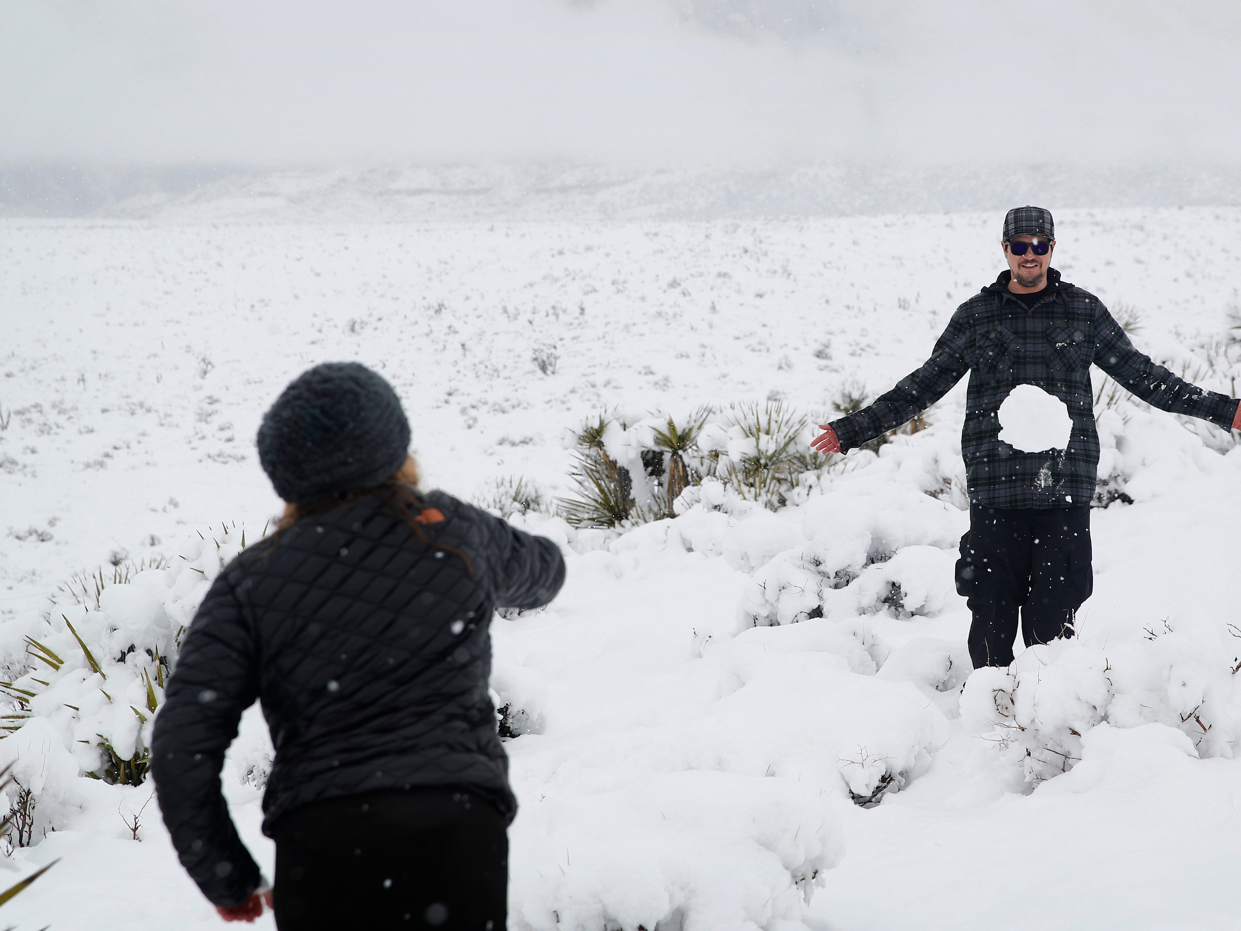 Nancy Knapp, left, throws a snowball at her son Zak Bagans at Red Rock National Conservation Area after a winter storm dropped several inches of snow, Thursday, Feb. 21, 2019, near Las Vegas. Bagans is the host of the the TV show Ghost Adventures. (AP Photo/John Locher)