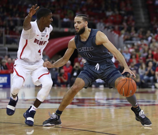 Nevada's Caleb Martin looks for room around Fresno State's Braxton Huggins during the teams' game earlier this season in Fresno.