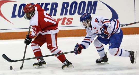 Penfield's Sean Smith moves the puck down ice against Fairport's Caleb Kaiser.