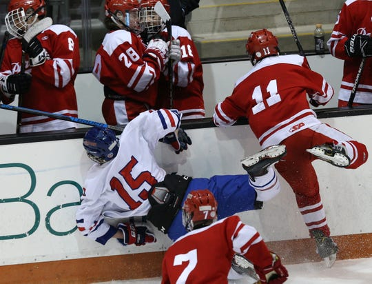 Penfield's Connor Stuewe (11) draws a five-minute penalty for a hit on Fairport's Connor Diem.