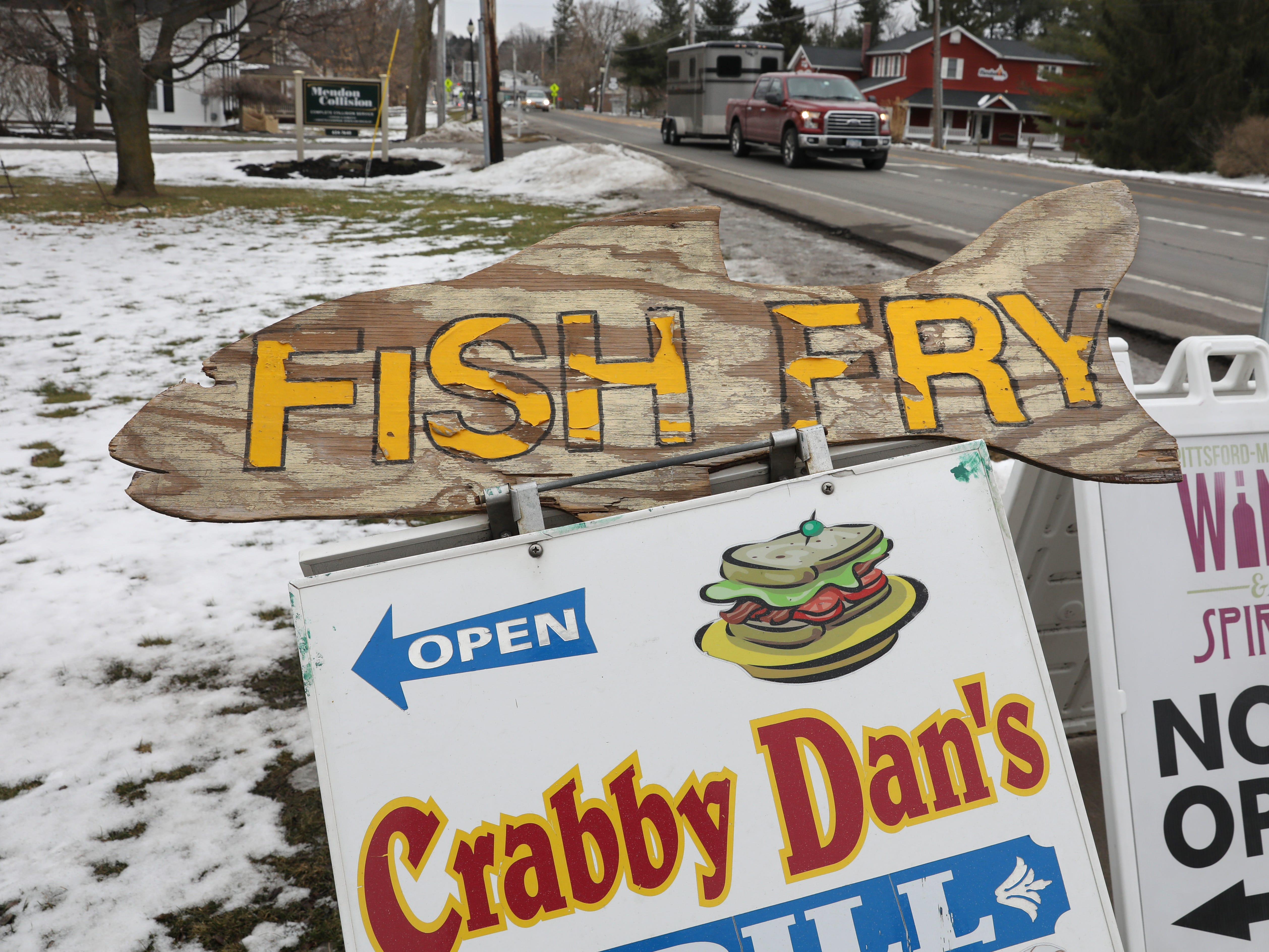 An A-frame sign points the way to the fish fry at Crabby Dan's Grill in Mendon.