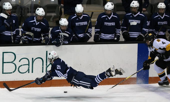 Pittsford's Zack Quinton (21)  is upended by McQuaid's Ryan McEvily during a Section V Class A semifinal on Thursday night. Pittsford won 4-2.