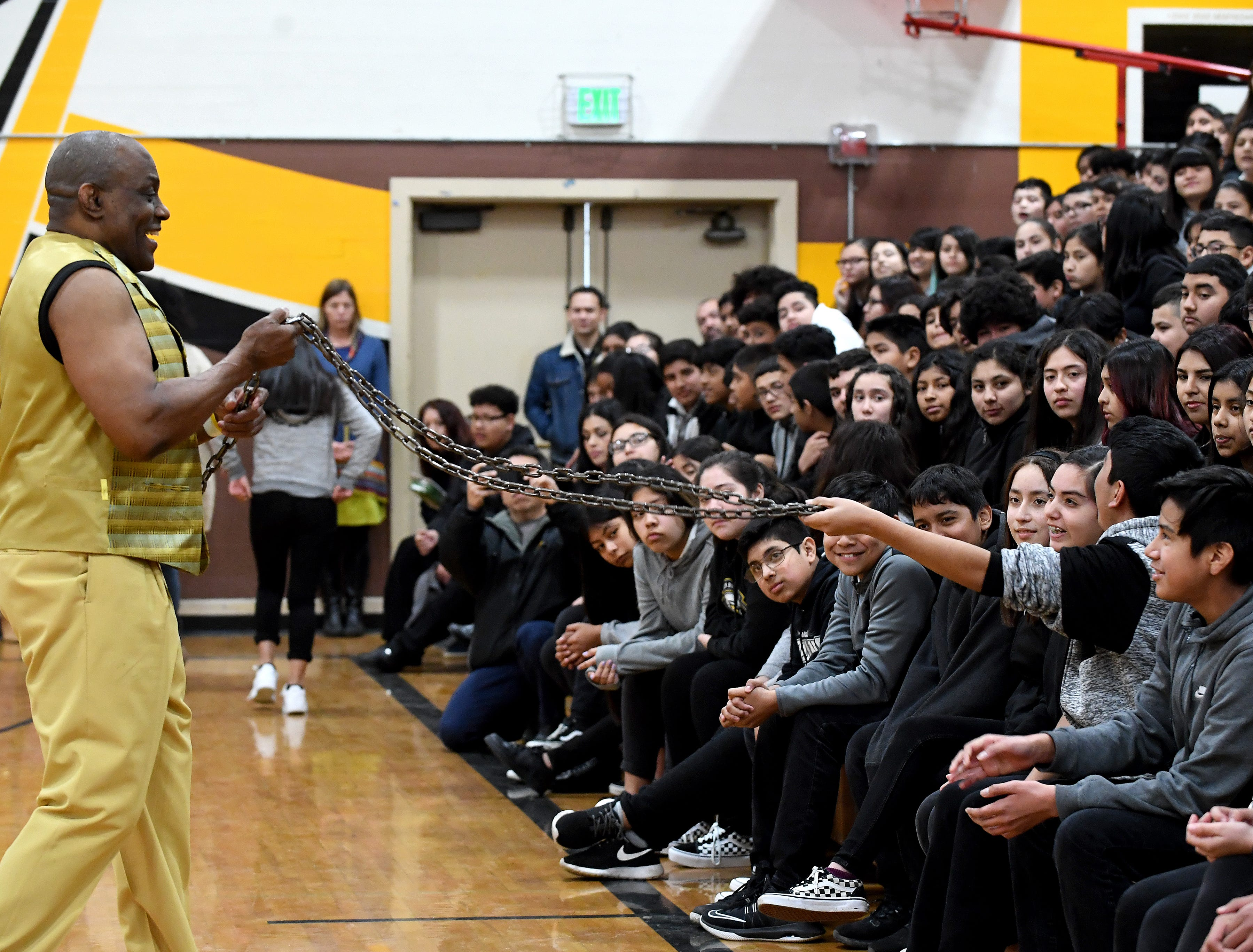 James Thompson lets students at El Sausal Middle School feel the weight of the chain he performs with during a visit to the school on FEb. 21, 2019.