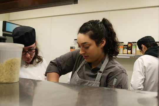 Sous chef Christina Morales demonstrates a technique to a student.