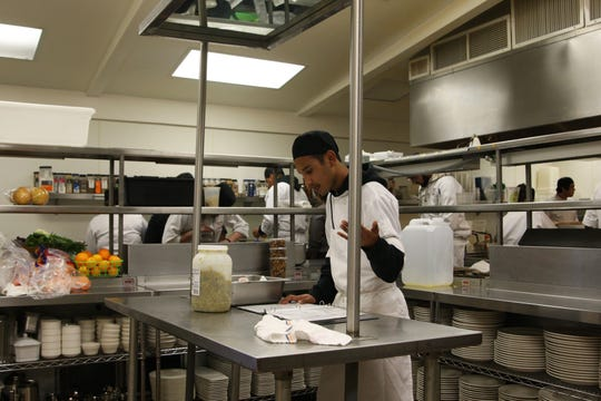 Rancho Cielo student Joaquin Pimentel studies the menu in the kitchen before the Friday evening service begins.