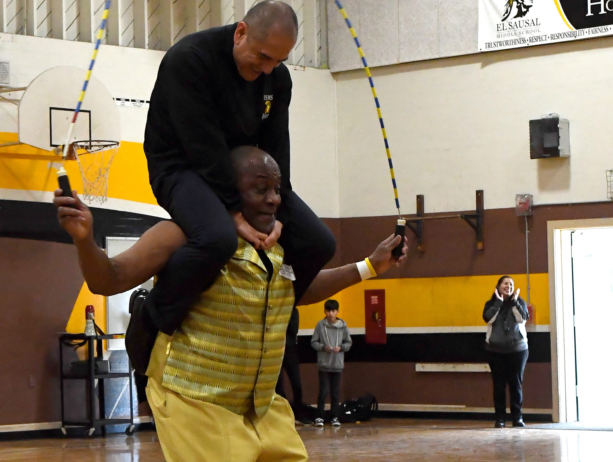 El Sausal Middle School Principal Francisco Huerta sits on James Brewster's shoulders during his visit to the school on Feb. 21, 2019.