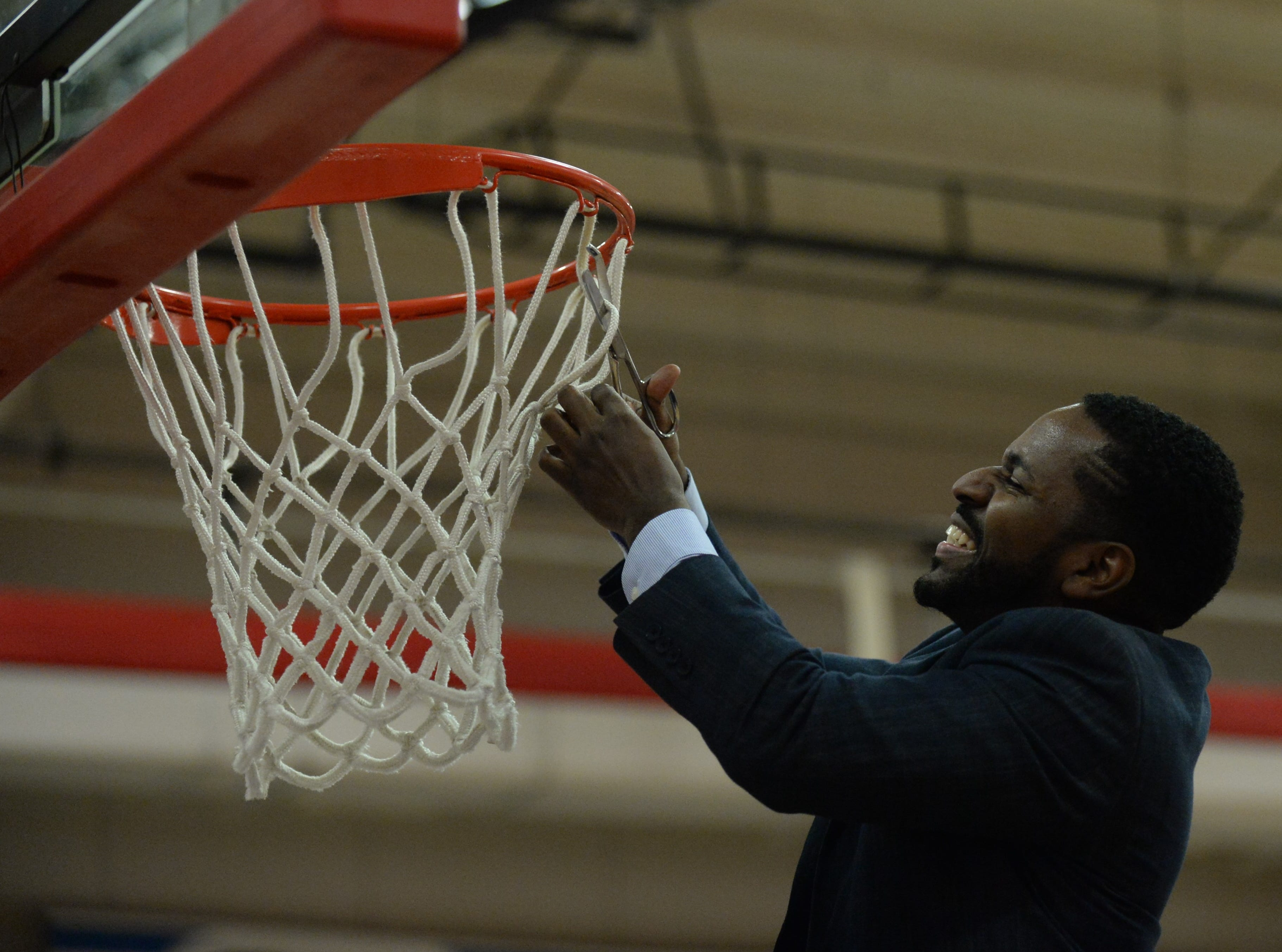 Delmarva Christian coach Jedidiah Roach cuts down the net after his team defeated Worcester Prep in the ESIAC Championship game on Thursday, Feb. 21, 2019.