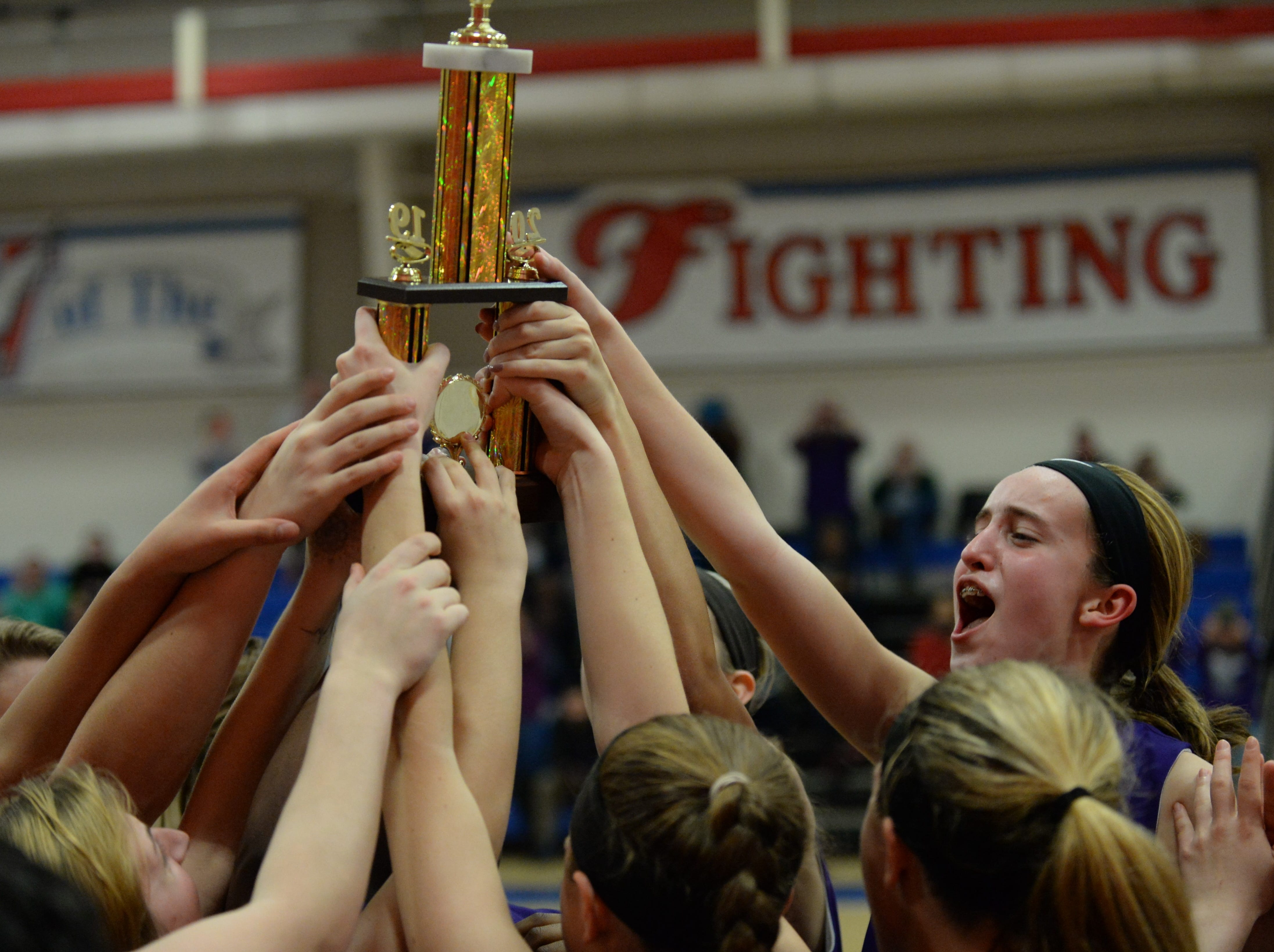 Delmarva Christian players hoist the championship trophy after defeating Worcester Prep in the ESIAC Championship game on Thursday, Feb. 21, 2019.