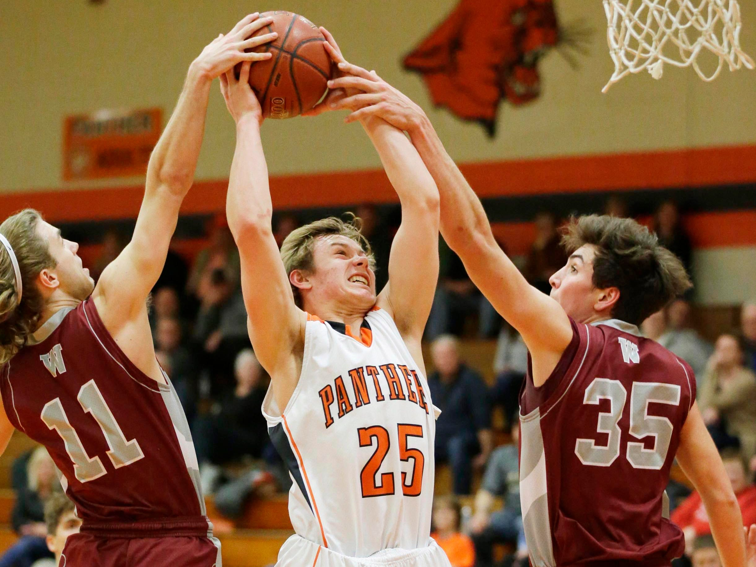 Winneconne's Marshal Scheider (11) and Greg Murawski (35) tag team to block Plymouth's Aiden Reilly (25) from making a shot, Wednesday, February 21, 2019, in Plymouth, Wis.