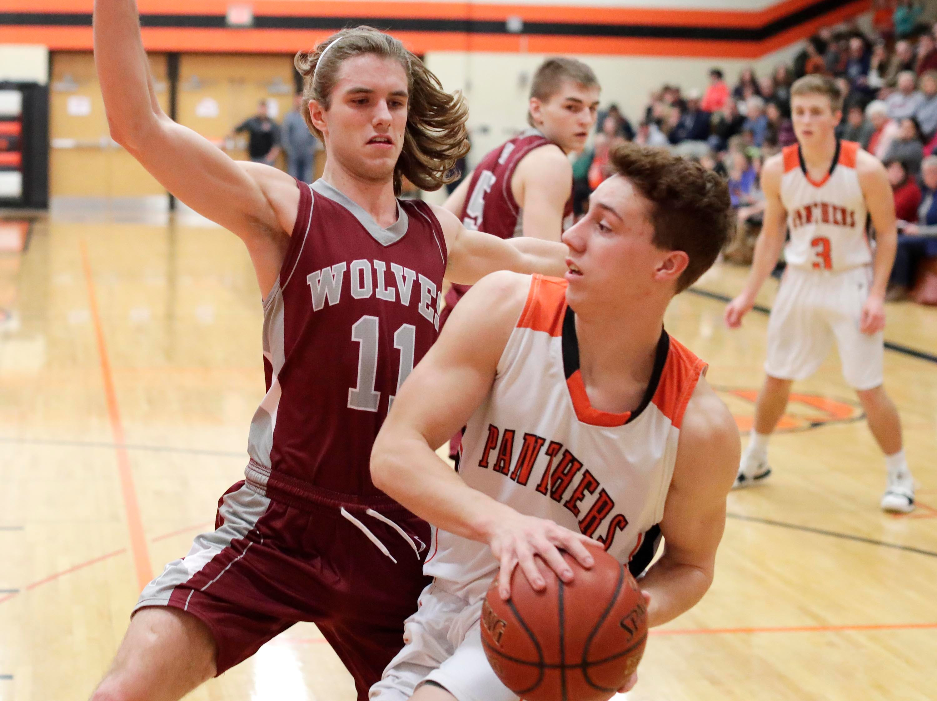 Plymouth's Sam Shutter (5) drives the ball by Winneconne's Marshall Scheider (11), Wednesday, February 21, 2019, in Plymouth, Wis.