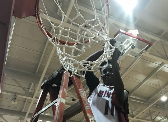 Minden's Shaniah Washington cuts down the nets following the Lady Tiders' win over DeRidder Thursday night.