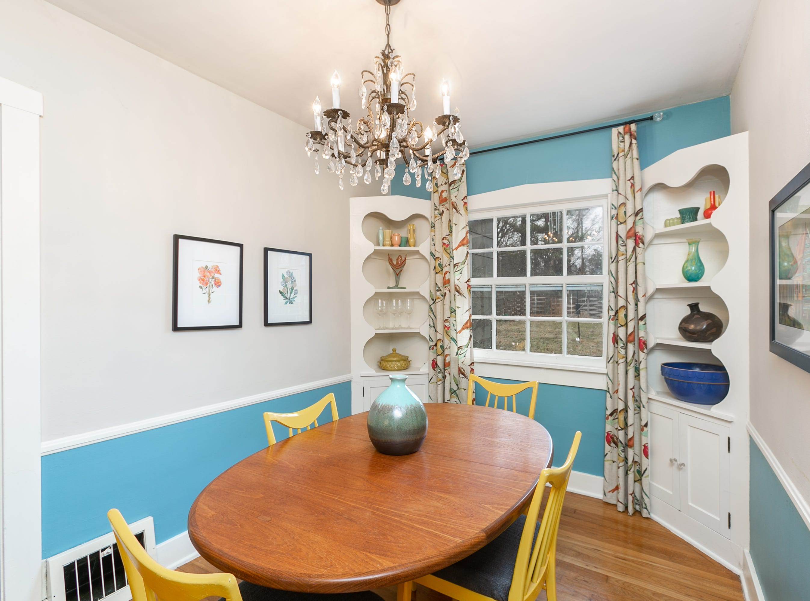 The dining room is painted with a vibrant turquoise accent. The yellow chairs and corner cabinet décor provide additional pops of color.