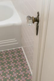 The bathroom's original features include floor and wall tile, the door handle and the medicine cabinet. Adie hand blended a soft pink to pull it all together.