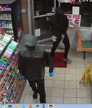 Two armed robbers are shown entering the Speedy Food Mart in February.
