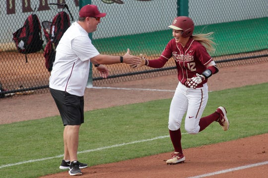 Florida State Seminoles infielder Carsyn Gordon (12) high-fives assistant coach Travis Wilson after she hit a home run. The Florida State Seminoles host the Elon Phoenixes for the Unconquered Tournament, Friday Feb. 22, 2019.