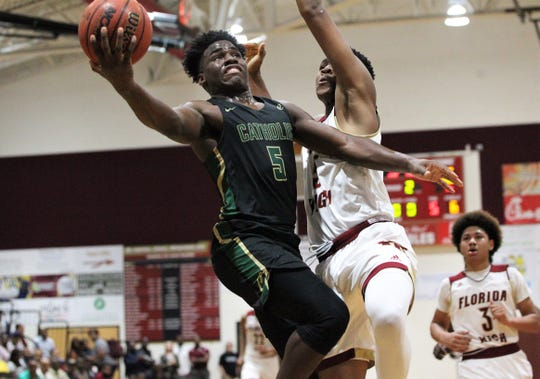 Pensacola Catholic's Ja'kobi Jackson goes up for a layup while guarding against a block from Florida High's Jaylen Martin as the Seminoles beat the Crusaders 47-42 during a Region 1-5A quarterfinal on Feb. 21, 2019.