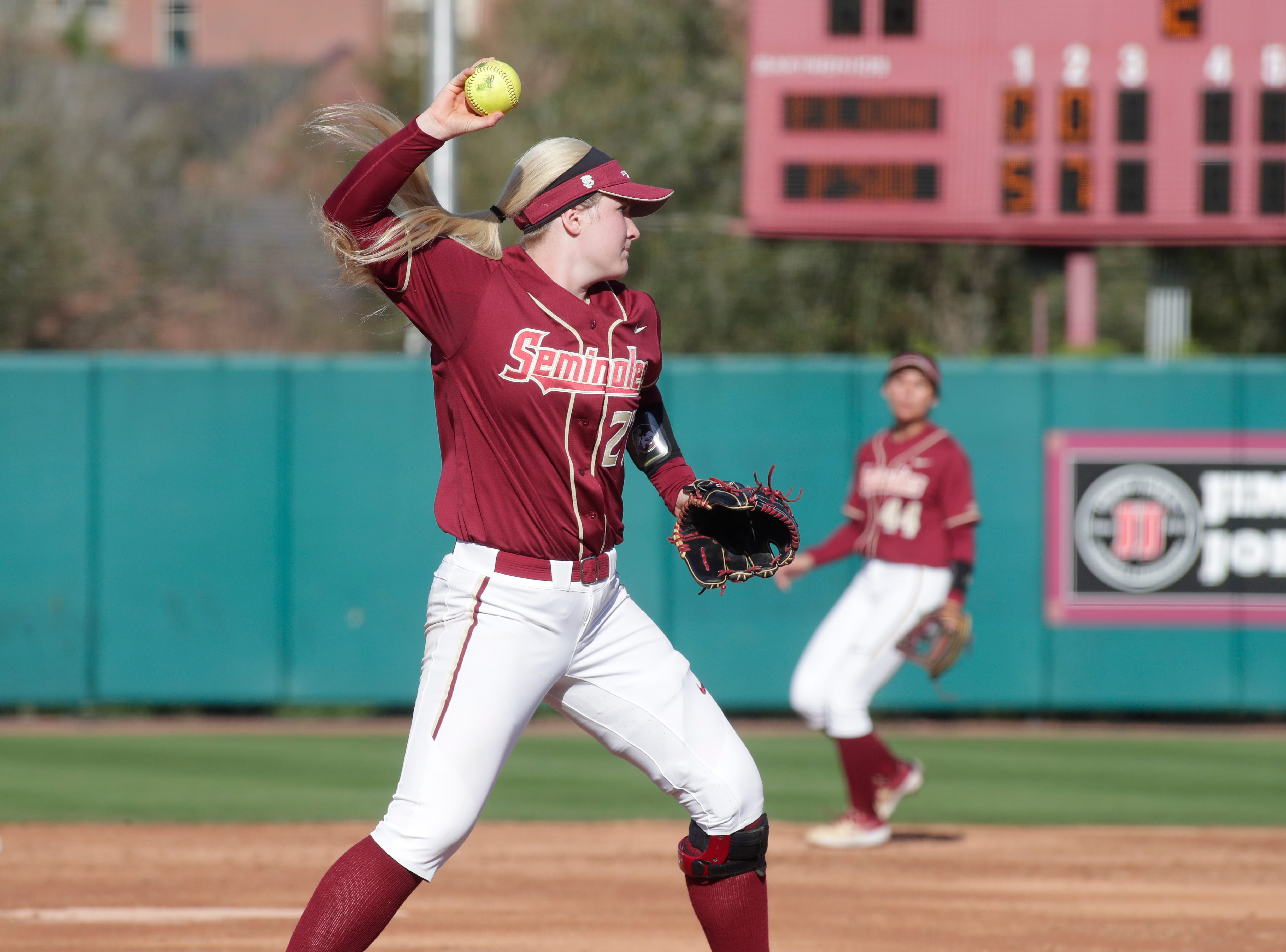 Florida State Seminoles pitcher Kara Bilodeau (27) picks up a ground hit to throw the ball to first base. The Florida State Seminoles host the Elon Phoenixes for the Unconquered Tournament, Friday Feb. 22, 2019.