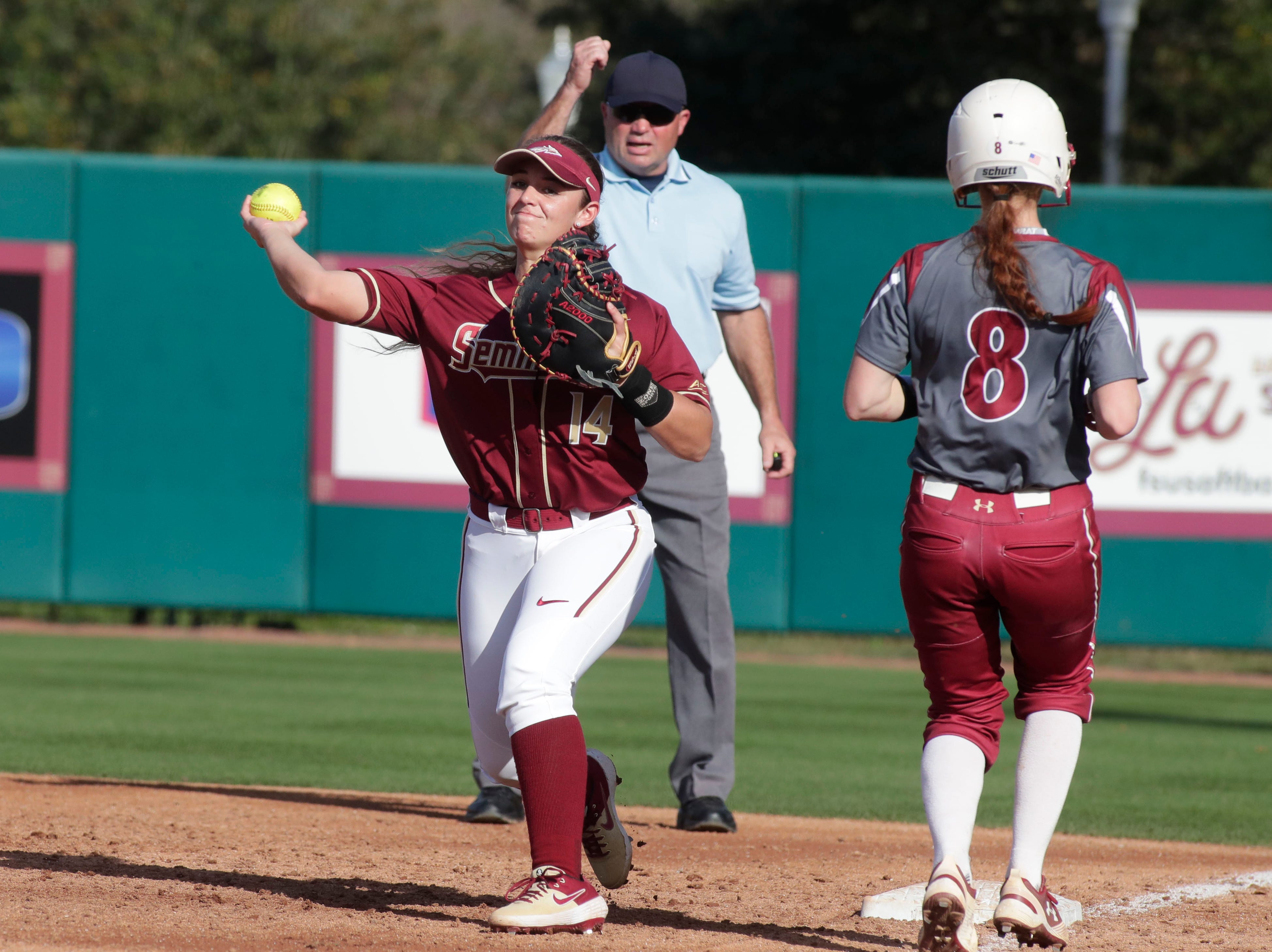 Florida State Seminoles utility player Savannah Parker (14) throws to home after getting the out at first base. The Florida State Seminoles host the Elon Phoenixes for the Unconquered Tournament, Friday Feb. 22, 2019.