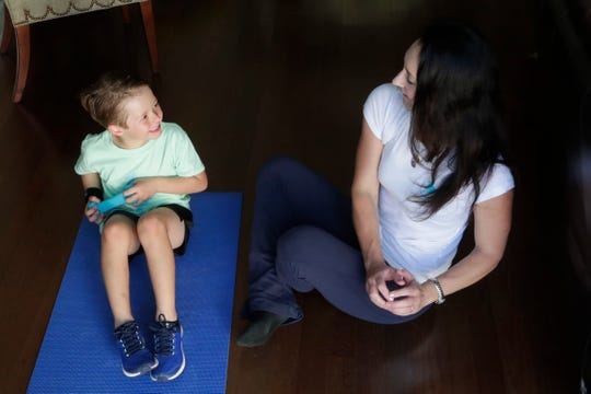 Cole Miller, 6, left, does Russian twists with his mother, Michelle Miller, on Thursday, Feb. 21, 2019. Miller is the founder and CEO of My First Workout. This program was created for parents to exercise with their children.