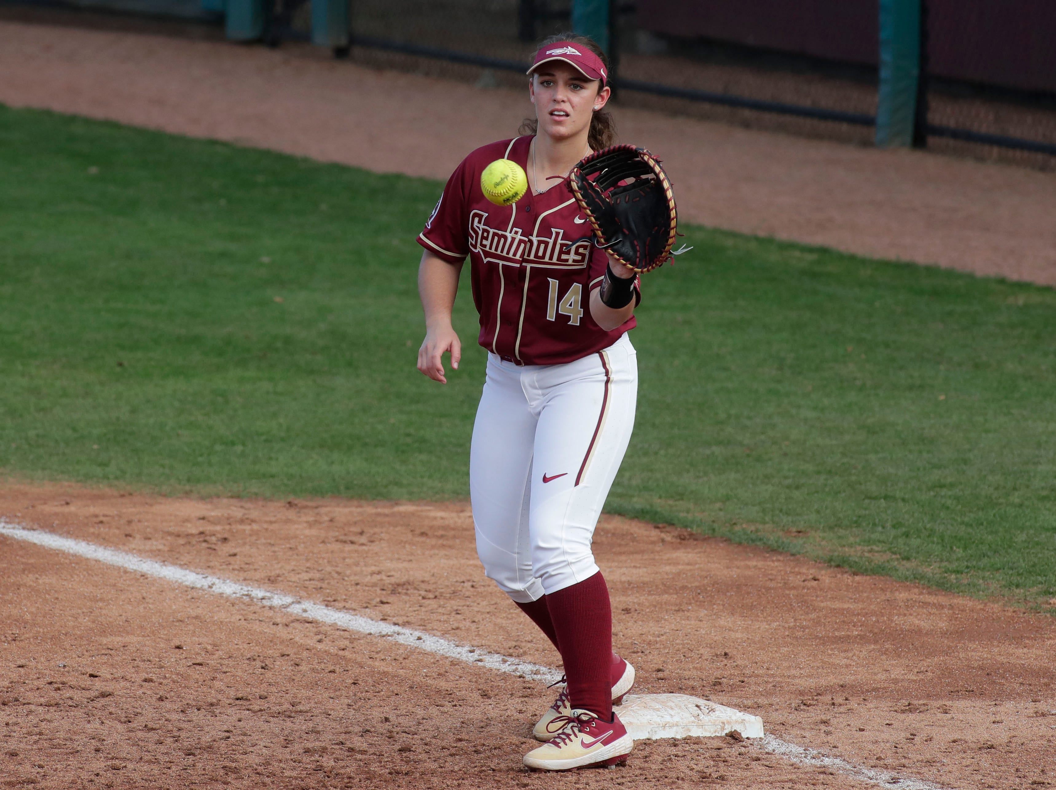 Florida State Seminoles utility player Savannah Parker (14) catches the ball at first base to get an out. The Florida State Seminoles host the Elon Phoenixes for the Unconquered Tournament, Friday Feb. 22, 2019.