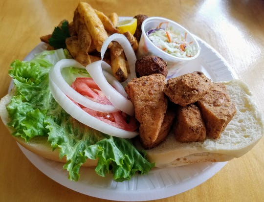 A lightly fried mahi sandwich is served with French fries, coleslaw and hush puppies at Tausha's Seafood.